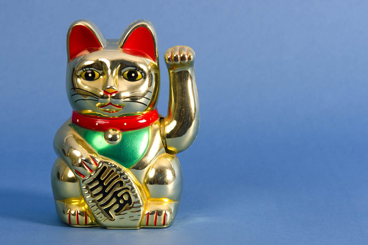 Beckoning cat holding a gold coin